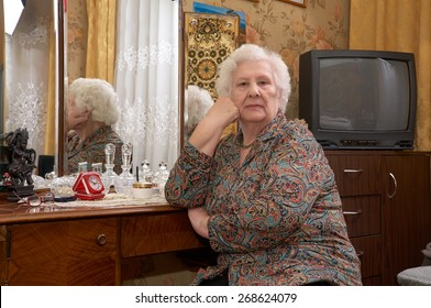 Portrait of senior caucasian woman about ninety years old sitting near the mirror and looking into the camera in her bed room