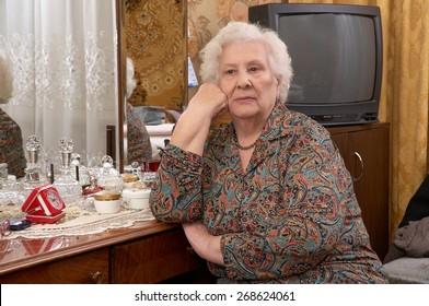 Portrait of senior caucasian woman with white hair about ninety years old sitting near the mirror in her bed room