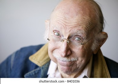 Portrait of a senior citizen wearing glasses and a jean jacket in a studio.