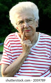 Portrait of a senior citizen woman outdoors in a thoughtful pose.