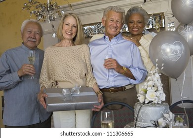 Portrait of senior couple celebrating 25th anniversary with friends