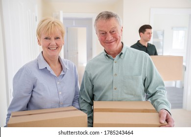 Portrait Of Senior Couple Downsizing In Retirement Carrying Boxes Into New Home On Moving Day With Removal Man Helping