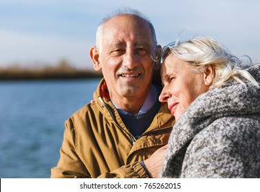 Portrait of senior couple embracing each other on a sunny autumn day.