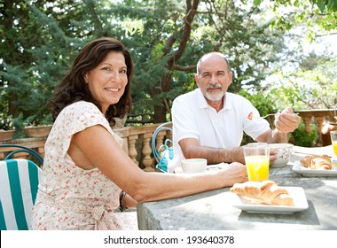 Portrait of a senior couple enjoying a healthy breakfast together in a luxury home garden on holiday. Mature people eating healthy food and enjoying each others company, outdoors. Travel lifestyle.