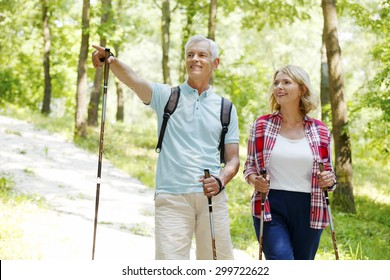 Portrait of senior couple enjoying a nordic walk. Active elderly woman and man walking on the forest and smiling.