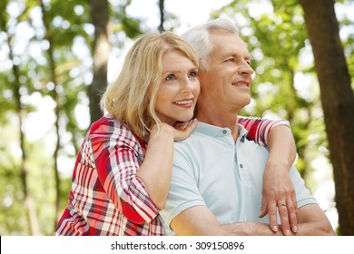 Portrait of senior couple hiking in the forest. Elderly woman embracing her senior man while standing outdoors and spending time together.