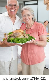 Portrait of senior couple holding chicken roast in the house