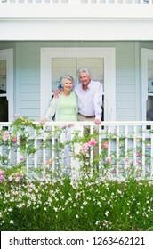Portrait of senior couple at home on verandah overlooking garden