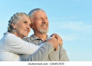 Portrait of senior couple hugging against blue sky