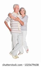 Portrait of senior couple hugging on white background, full length