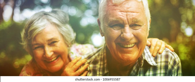 Portrait of senior couple laughing against trees in back yard