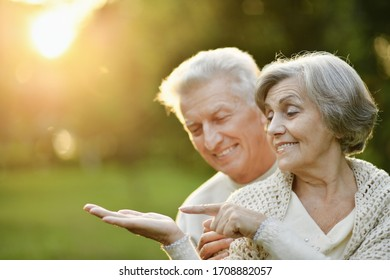Portrait of senior couple in the park showing something