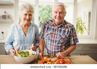 Portrait of senior couple preparing salad in kitchen