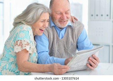 Portrait of senior couple reading newspaper at home