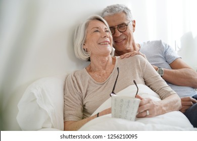 Portrait of senior couple relaxing in bed
