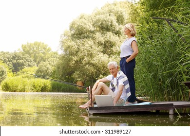 Portrait of senior couple relaxing at shore. Elderly woman and man fishing at lake while retired man showing something to her wife on laptop.