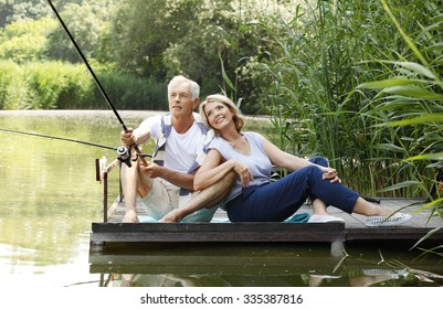 Portrait of senior couple relaxing together and the lakeside and fishing while sitting at the pier.