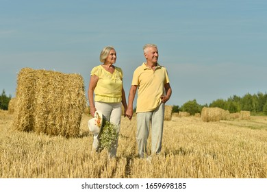Portrait of senior couple resting at summer field during vacation