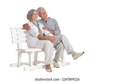 Portrait of senior couple sitting on bench on white background