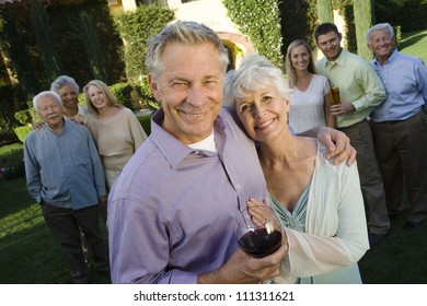 Portrait of senior couple standing with family and friend in background