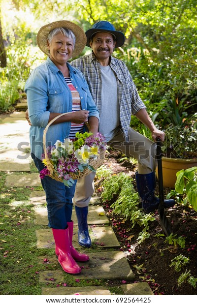 Portrait of senior couple standing in garden on a sunny day