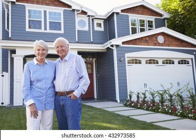 Portrait Of Senior Couple Standing Outside House