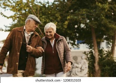 Portrait of senior couple talking and walking outdoors on winter day. Elderly man holding hand of his female partner and walking on street.