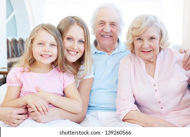 Portrait of senior couple with their daughter and granddaughter looking at camera