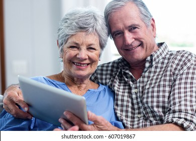 Portrait of senior couple using a digital tablet at home