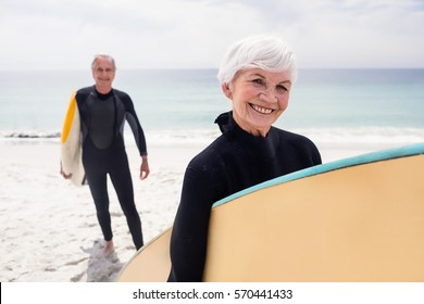 Portrait of senior couple in wetsuit holding surfboard on beach on a sunny day