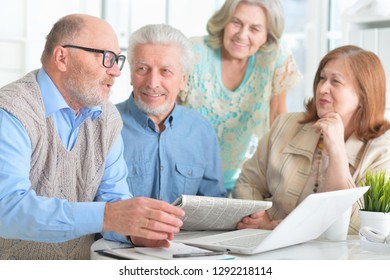 Portrait of senior couples working with laptop and reading newspaper