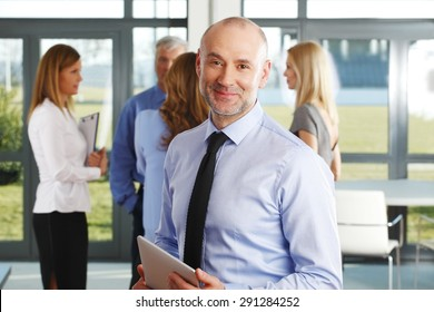 Portrait of senior director holding hand digital tablet while standing at office building. Group of business people standing at background.
