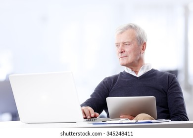 Portrait of senior director sitting at office desk and working online while using digital tablet and laptop.