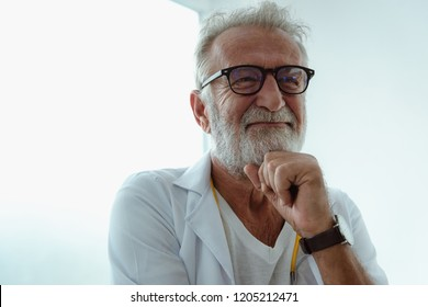 Portrait of senior doctor posing arms cross with little smilling in his office.