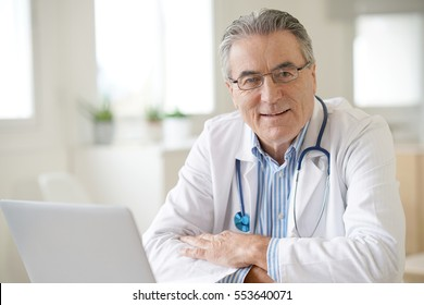 Portrait of senior doctor sitting in medical office