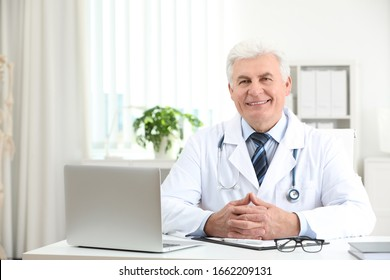 Portrait of senior doctor in white coat at workplace