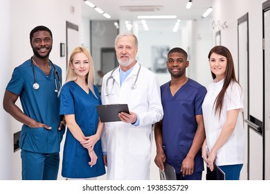 Portrait of senior doctor in white uniform and young doctors therapists posing looking at camera