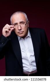 portrait of senior earnest man in glasses over dark background