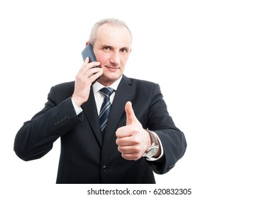 Portrait of senior elegant man talking at phone showing like gesture wearing suit and tie isolated on white background with copy text space