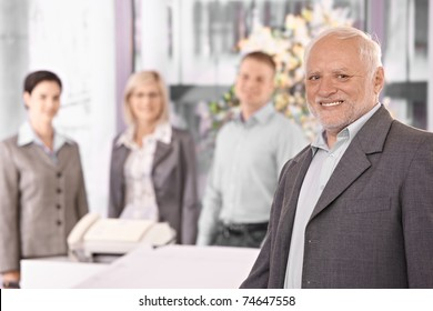 Portrait of senior executive businessman smiling at camera, with team standing in background.?