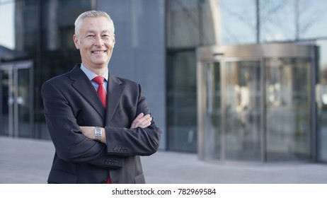 Portrait of senior executive smiling to camera, with space for text