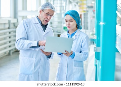 Portrait of senior factory worker wearing lab coat training young woman and using laptop while standing in clean production workshop of modern plant
