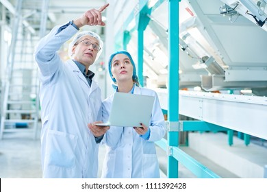 Portrait of senior factory worker wearing lab coat explaining rules to female trainee and pointing up while standing in clean production workshop of modern plant, copy space