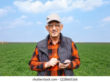 Portrait of senior farmer in filed looking at camera and holding phone in his hand during the sunny day.