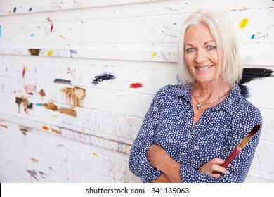 Portrait Of Senior Female Artist Against Paint Covered Wall