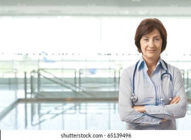 Portrait of senior female doctor on hospital corridor looking at camera smiling. Copy space on left.?