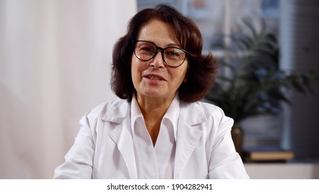 Portrait of senior female doctor wearing white coat consulting patient online. Aged woman practitioner in eyeglasses having online conference with patient or colleague. Telemedicine concept