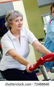 Portrait of senior female doing physical exercise on special equipment