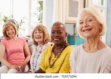 Portrait Of Senior Female Friends Relaxing On Sofa At Home