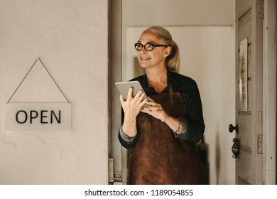 Portrait of senior female goldsmith standing at workshop entrance with digital tablet. Female jeweler wearing apron and holding a tablet pc at workshop door.